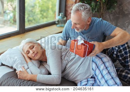 Special day. Pleasant aged woman sleeping in bed while her smiling husband sitting nearby and holding a birthday present
