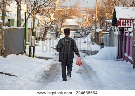 Homeless man is walking on the road in winter .