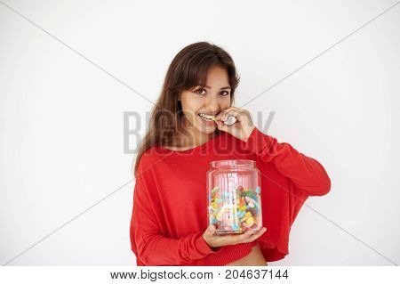 Gluttony and unhealthy diet concept. Picture of beautiful young brunette female eating jellybeans or marmalades out of big glass jar looking at camera with joyful expression on her pretty face