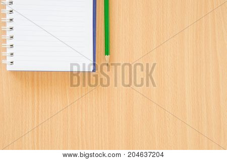 White note book and green pencil on beech color background with copy space.