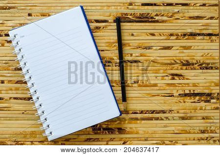 White note book and black pencil on bamboo color background with copy space.