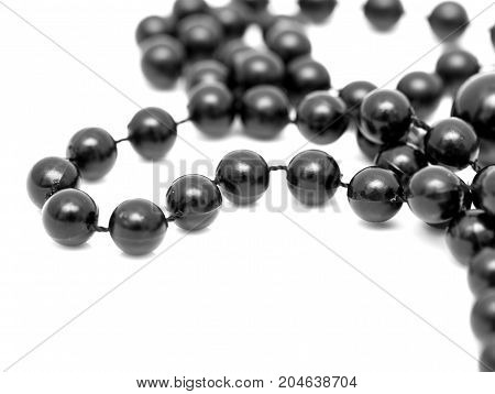 Black beads on a rope on a white background
