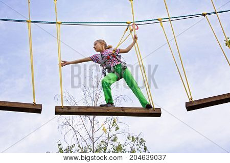 Teenage girl walking on a board on a rope park