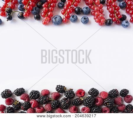 Black-blue and red berries isolated on white. Ripe blueberries blackcurrants blackberries and red currants raspberries. Berries at border of image with copy space for text. Background berries. Top view. Various fresh summer berries on white background.