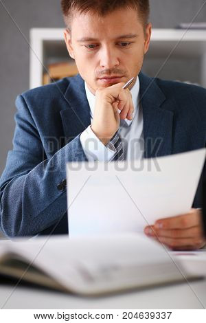 Serious Businessman In The Office Examines Documents