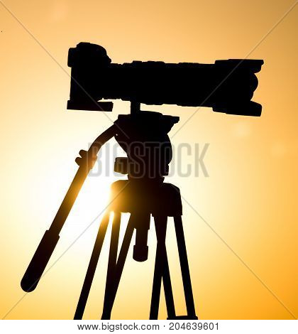 Silhouette of a camera on a tripod at sunset .