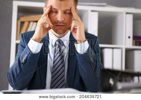 A Man Experiences Stress And A Headache In The Workplace