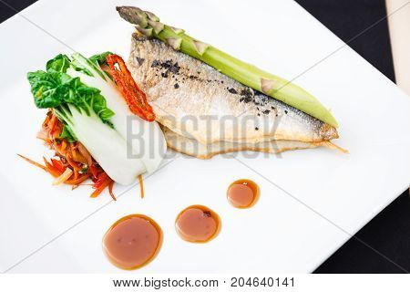 Bream fish with asparagus, vegetables, fried wok and Teriyaki sauce