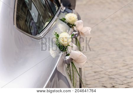 Side View Of A Wedding Car Decorated With White Roses Ready To Carry Just Married Couple Directly To