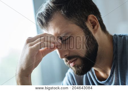 I feel pain. Moody nice young man holding a bridge of his nose and closing his eyes while feeling pain
