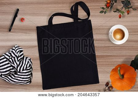 Black blank cotton eco tote bag with autumn decorations, cup of coffee and scarf, design mockup for Thanksgiving, Halloween bags.
