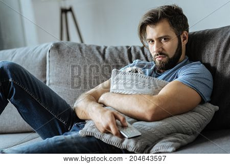 Absolute apathy. Depressed moody young man holding a cushion and watching TV while resting on the sofa