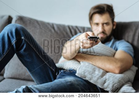 TV channels. Selective focus of a TV remote control being used by a nice sad gloomy man while switching TV channels