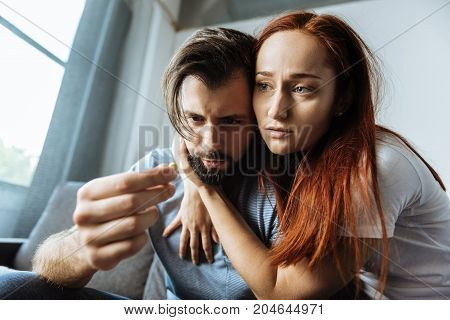 I am with you. Pleasant cheerless young woman sitting together with her boyfriend and hugging him while showing her love