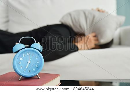 Sleepy Asian Business woman in black shirt covering ears with pillow on sofa and Alarm clock Notebook on side table. Female having trouble waking up. Stress from overtime working concept.
