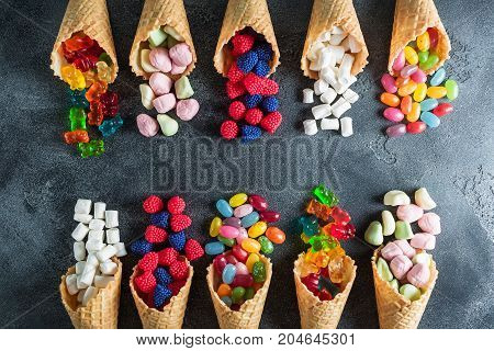 Assorted candy in waffle cones. Summer food concept. Flat lay, top view