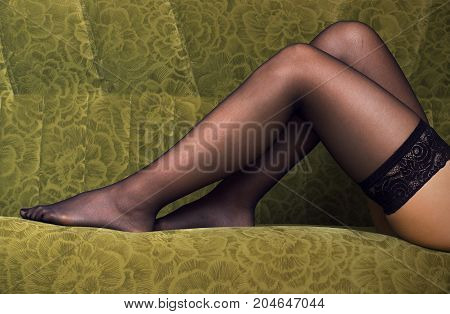 Sexy female legs in black stocking on green sofa background.