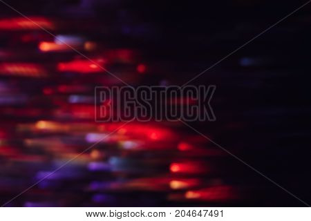 Abstract background of colorful lines in motion on black. Bokeh of defocused blurs, neon blue, orange and red leds, glowing city lights, wallpapers and banners