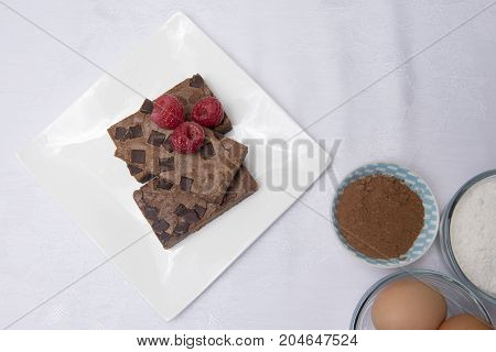 Chocolate brownie slices with raspberries, coco powder and eggs.