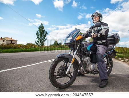 elderly motorcyclist wearing a jacket and glasses with a helmet sitting on his motorcycle on the open road