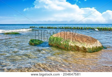 sea waves break down on a large stone on sunny summer day