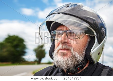 portrait of elderly motorcyclist wearing a jacket and glasses with a helmet on sunny summer day outdoor closeup