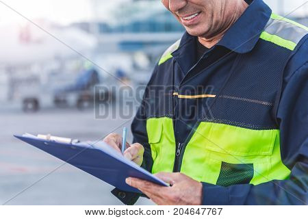 Focus on close up male worker arms writing document while standing outdoor at airport