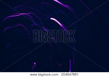 Abstract background of violet lines in motion on black. Bokeh of defocused curves spinning into spiral, blurred neon leds, festive backdrop of serpentine, holidays and celebrations