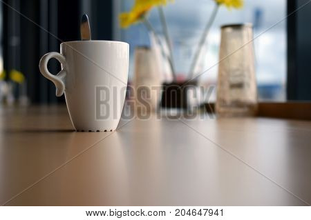 Mug of coffee on table in cafe. Focus on cup on foreground, yellow flowers on background.