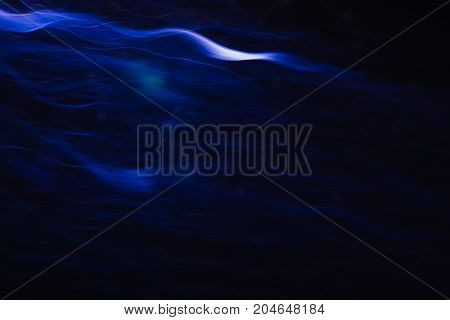 Abstract background of white waves in motion on black. Bokeh of defocused curves, blurred neon leds, similar to tobacco smoke, backdrop of addictions and acquired habits
