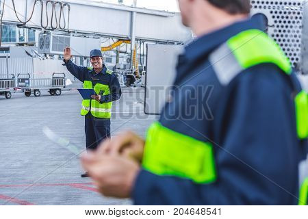 Hey, I am here. Full length portrait of cheerful male worker flourishing hand to partner while looking on him. He keeping clipboard