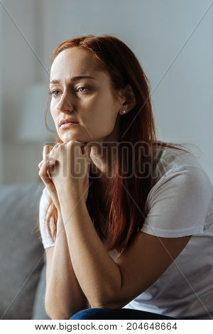 Bad mood. Depressed sad young woman holding her chin and thinking about her life while feeling unhappy