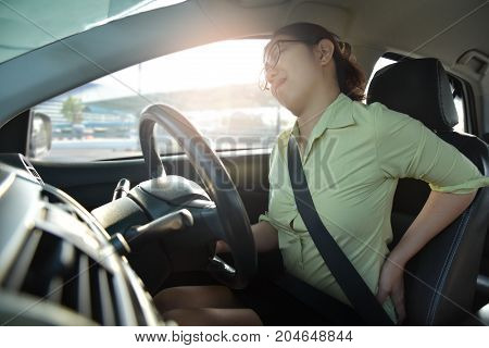 Asian glasses business woman having back pain while driving a car. Illness disease for overtime working concept.