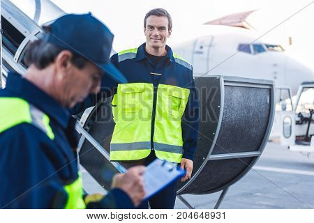 Portrait of cheerful young man having job at airport. He looking on colleague who writing document