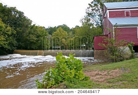water pours over a low dam next to a red gristmill