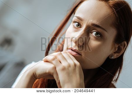 Problems in life. Sad attractive red haired woman holding her chin and feeling upset while having personal problems in life