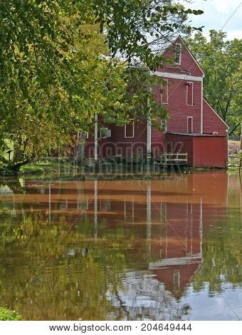 a red gristmill reflected in a muddy stream