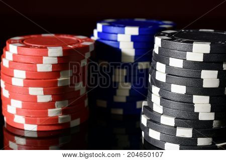 Red, blue and black poker chips close up on reflective black table.