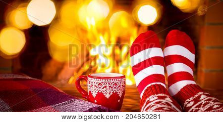 Woman in Christmas socks near fireplace. Person relaxing at home. Winter holiday Xmas and New Year concept