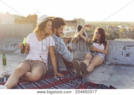 Young people chilling out and partying at a building rooftop