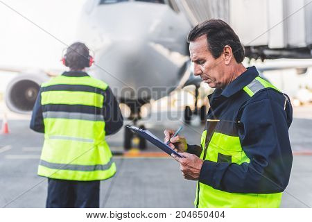 Side view serious mechanic noting document. Colleague looking at plane while turning back to camera