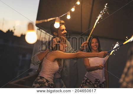 Group of young friends having fun at a rooftop party. Focus on the girl on the right