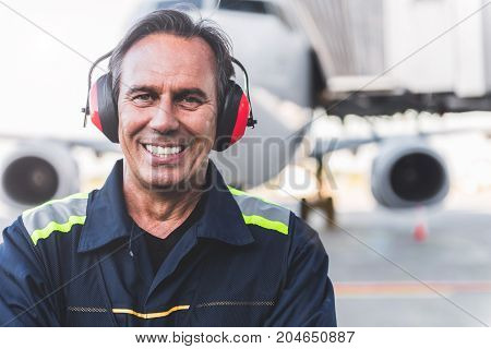 Portrait of worker expressing happiness while situating at outdoor airport. He looking at camera. Copy space
