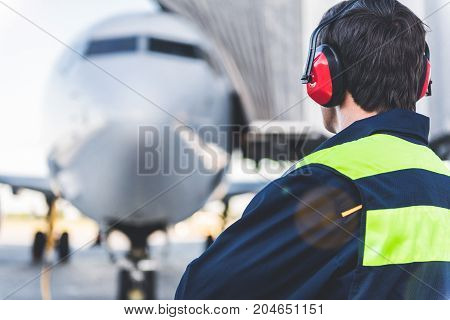 Mechanic working in headset at airport. He looking at plane while turning back to camera