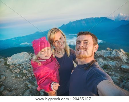 Family hikers making selfie on a top of mountain against mountains valley background. Tourist are laughing and happy.