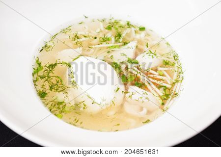 Chicken broth with homemade noodles, vegetables and poached egg