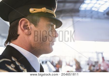 Side view male pilot expressing calmness while locating at airdrome. Occupation concept. Copy space