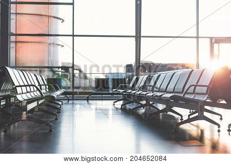 Long cozy benches situating opposite each other in spacious airport hall with glass wall