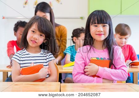 Two Asian girl kid hugging book and smiling in classroom and while teacher teach friends beside themkindergarten education.