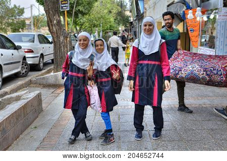 Fars Province Shiraz Iran - 18 april 2017: Three Iranian schoolgirls in school uniform with a white hijab on a city street.